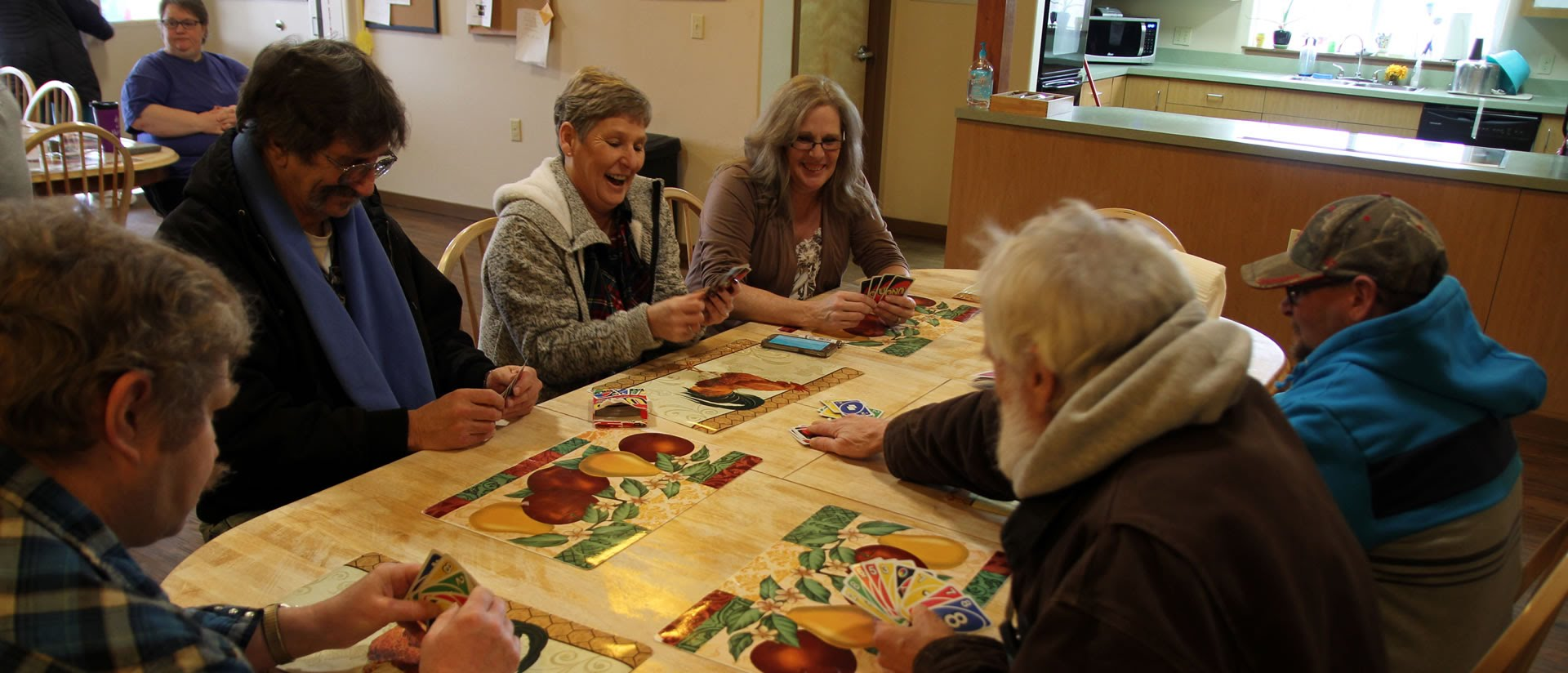 Residents and staff playings cards in Harmony House III kitchen